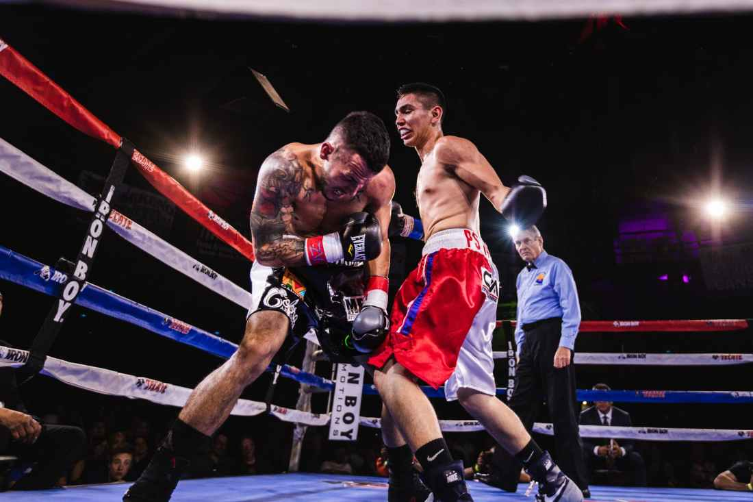 low angle photo of two men fighting in boxing ring